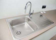 Chiuda su sul lavandino di cucina moderno del rubinetto del metallo della cucina e del metallo immagini stock libere da diritti