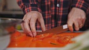 Chiuda su sul taglio del pomodoro sul bordo di plastica nella cucina Nutrizione e alimento biologico stock footage