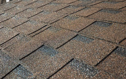Chiuda su sul tetto marrone delle assicelle dell'asfalto Costruzione del tetto fotografie stock libere da diritti