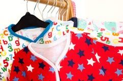 Chiuda su sul vestire il gabinetto con i vestiti sistemati sui ganci Immagine Stock Libera da Diritti