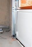 Chiuda su sull'installazione della porta del garage Immagini Stock