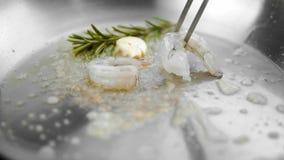 Chiuda su sulla cottura del gamberetto su una pentola con burro con aglio e rosmarini video d archivio
