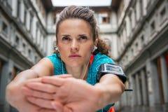 Chiuda su sulla giovane donna sportiva con l'allungamento delle cuffie Fotografia Stock