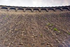 Chiuda su sulla parete di pietra della diga Immagine Stock
