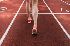 Chiuda su sulle belle gambe femminili con le scarpe rosa sulla pista corrente Immagini Stock Libere da Diritti