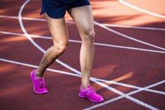 Chiuda su sulle belle gambe femminili con le scarpe rosa sulla pista corrente Fotografia Stock Libera da Diritti