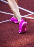Chiuda su sulle belle gambe femminili con le scarpe rosa sulla pista corrente Immagine Stock