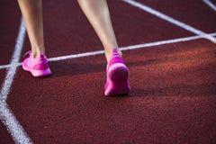 Chiuda su sulle belle gambe femminili con le scarpe rosa sulla pista corrente Immagine Stock Libera da Diritti