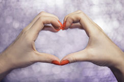 Chiuda su sulle belle mani femminili con il manicure rosso nella forma del cuore di amore Immagine Stock Libera da Diritti