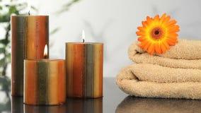 Chiuda su sulle candele, sugli asciugamani e sul girasole stock footage