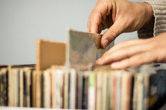 Chiuda su sulle mani che passano in rassegna il negozio di dischi Fotografia Stock
