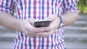 Chiuda su sulle mani del ` s dell'uomo che passano in rassegna lo smartphone colpo del cursore video d archivio