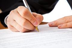 Chiuda in su sulle mani dell'uomo d'affari che firmano un contratto Fotografia Stock Libera da Diritti