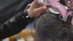 Chiuda su taglio di capelli al negozio di barbiere con le forbici video d archivio