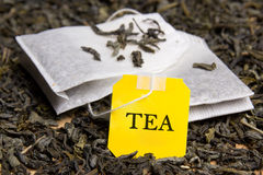 Chiuda su un'immagine di due bustine di tè e delle foglie di tè secche Immagini Stock Libere da Diritti