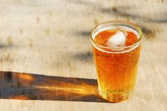 Chiuda su su un vetro della pinta della birra ambrata di Pale Ale, gettante un'ombra su una vecchia tavola di legno immagine stock