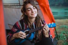 Chiuda su una donna la chitarra del gioco che dopo sveglia immagini stock