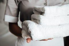 Chiuda su una giovane degli asciugamani piegati della domestica tenuta Fotografia Stock Libera da Diritti