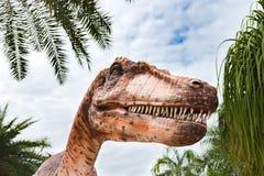 Chiuda su su una statua realistica del tirannosauro nel parco del dinosauro immagini stock libere da diritti