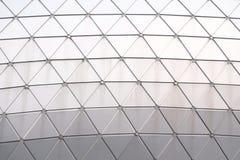 Chiuda su una superficie di vetro di un modello del triangolo dentro un'alta costruzione nella citt? immagine stock
