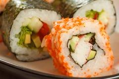 Chiuda su Uramaki la California Rotolo di sushi con il nori, riso, pezzi Fotografie Stock Libere da Diritti