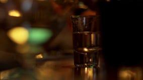 Chiuda su vetro con la condizione sparata vodka sulla tavola sulla mano maschio di versamento del fondo archivi video