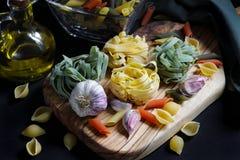 Chiuda sugli ingredienti scuri della pasta dell'alimento del chiaroscuro con le tagliatelle fotografie stock