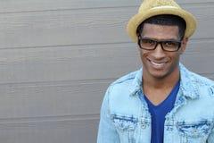 Chiuda sugli occhiali d'uso sorridenti del giovane uomo di colore, esaminanti la macchina fotografica contro Gray Wall Background Fotografia Stock Libera da Diritti