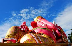 Chiuda sui bei grandi colori rosa di signore indù Ganesha del dio con il fondo bianco del cielo blu e della nuvola Fotografie Stock