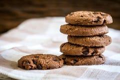 Chiuda sui biscotti di pepita di cioccolato impilati sul tovagliolo con la b di legno Fotografia Stock