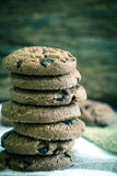 Chiuda sui biscotti di pepita di cioccolato impilati sul tovagliolo con di legno Fotografie Stock Libere da Diritti