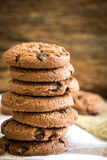 Chiuda sui biscotti di pepita di cioccolato impilati sul tovagliolo con la b di legno Immagini Stock