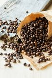 Chiuda sui chicchi di caffè arrostiti in sacchi di carta su fondo di legno Immagine Stock Libera da Diritti
