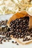 Chiuda sui chicchi di caffè arrostiti in sacchi di carta su fondo di legno Fotografie Stock