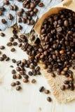 Chiuda sui chicchi di caffè arrostiti in sacchi di carta su fondo di legno Fotografia Stock Libera da Diritti