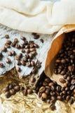 Chiuda sui chicchi di caffè arrostiti in sacchi di carta su fondo di legno Fotografie Stock Libere da Diritti
