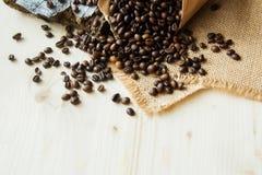 Chiuda sui chicchi di caffè arrostiti in sacchi di carta su fondo di legno Fotografia Stock