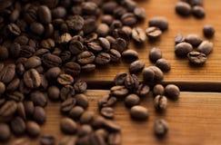 Chiuda sui chicchi di caffè sulla tavola di legno Fotografia Stock