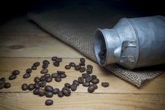 Chiuda sui chicchi di caffè, sulle borse del sacco e sui contenitori Immagini Stock