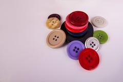 Chiuda sui colori assortiti sparsi impilati bottoni di cucito Fotografie Stock