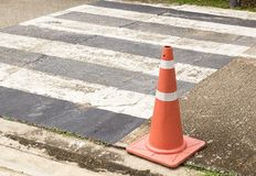 Chiuda sui coni arancio luminosi di traffico che stanno in una fila su asphal Fotografia Stock