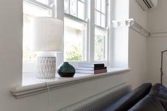 Chiuda sui dettagli dei libri della lampada e degli oggetti dell'ornamento sul si della finestra Fotografia Stock Libera da Diritti
