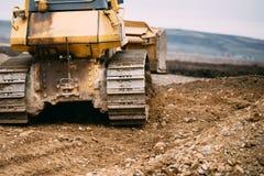 Chiuda sui dettagli del bulldozer che spingono la terra e che livellano la terra sul cantiere Immagini Stock Libere da Diritti