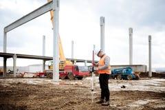 Chiuda sui dettagli del cantiere, ingegnere civile industriale che lavora con le colonne prefabbricate del cemento fotografia stock