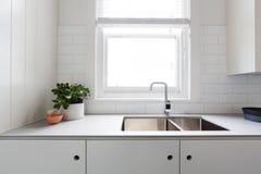 Chiuda sui dettagli della cucina bianca contemporanea con le mattonelle del sottopassaggio Immagine Stock Libera da Diritti