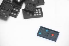 Chiuda sui domino neri di colore con i pezzi variopinti del punto Immagini Stock