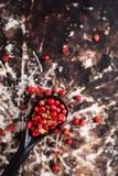 Chiuda sui granelli di pepe rosa organici o sulla bacca rosa in ceramico nero Fotografie Stock