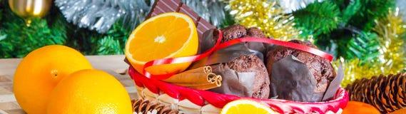 Chiuda sui maffins, sulle arance e sul cioccolato sul fondo dell'albero di Natale Immagine Stock Libera da Diritti