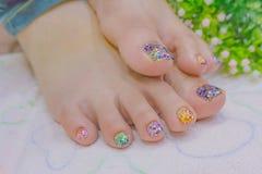 Chiuda sui piedi beuatiful della giovane donna con l'unghia del piede variopinta immagini stock