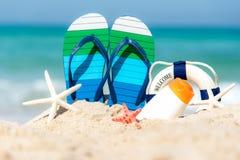 Chiuda sui sandali sulla spiaggia di sabbia con il blocchetto di somma e la spiaggia sabbiosa delle stelle marine Fotografia Stock Libera da Diritti